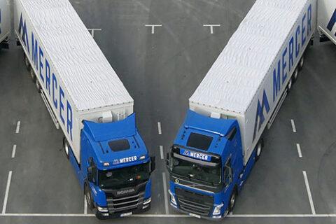"""Mercer Holz LKWs, die auf dem Parkplatz der Mercer Rosenthal Zellstofffabrik geparkt sind und das Mercer """"M"""" bilden"""