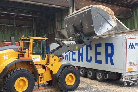 Frontlader kippt Hackschnitzel in einen Mercer Holz Chip-LKW, geparkt im Sägewerk von Mercer Timber Products in Friesau, Deutschland