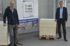 André Listemann, Geschäftsführer Mercer Stendal, steht mit Teammitgliedern und Zellstoffplattenstapeln zum Gedenken an die 10 Millionen Tonnen Produktion